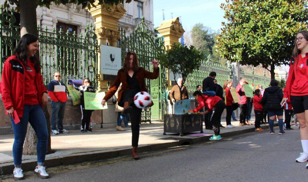 Lorena Gil a la entrada de la Junta del Principado jugando un partido de fútbol junto a jugadoras del Femiastur y el Gijón Femenino